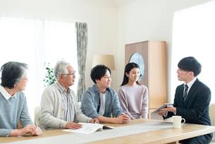 ビジネスマンと話をする2世代家族の写真素材 [FYI03045082]