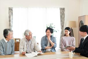 ビジネスマンと話をする2世代家族の写真素材 [FYI03045083]