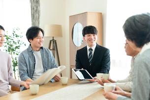 ビジネスマンと話をする2世代家族の写真素材 [FYI03045086]