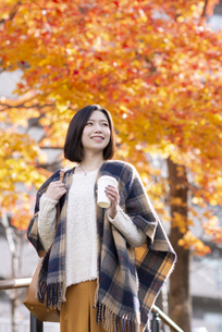 紅葉の前でコーヒーを持ち微笑む女性の写真素材 [FYI03045095]