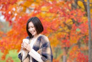 紅葉の前でコーヒーを持ち微笑む女性の写真素材 [FYI03045116]
