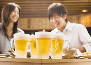 居酒屋でビールを飲むカップルの写真素材 [FYI03045722]