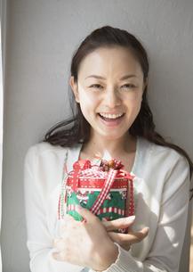 クリスマスプレゼントを持つ女性の写真素材 [FYI03046667]