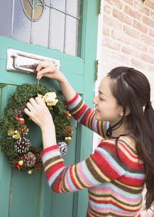 クリスマスリースを飾る女性の写真素材 [FYI03046670]