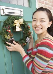 クリスマスリースを飾る女性の写真素材 [FYI03046678]