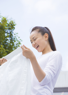 洗濯物を広げる女性の写真素材 [FYI03046721]