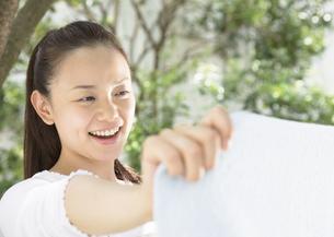 洗濯物を広げる女性の写真素材 [FYI03046735]