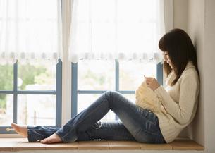 窓辺で編み物をする女性の写真素材 [FYI03046763]