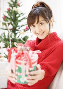 クリスマスプレゼントを差しだす女性の写真素材 [FYI03046772]