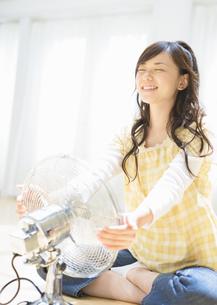 扇風機の前の女性の写真素材 [FYI03046813]