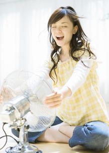 扇風機の前の女性の写真素材 [FYI03046814]