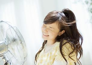 扇風機の前の女性の写真素材 [FYI03046829]