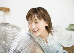 扇風機の前の女性の写真素材 [FYI03046912]