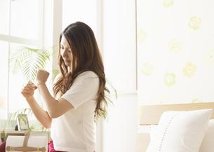 ブレスレットをつける若い女性の写真素材 [FYI03047209]