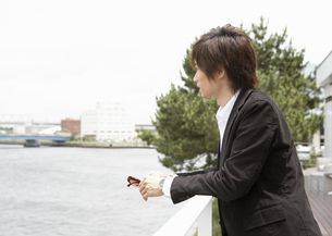 水辺を眺める若い男性の写真素材 [FYI03047618]