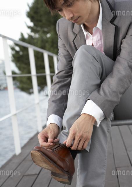 靴ひもを結ぶ若い男性の写真素材 [FYI03047653]