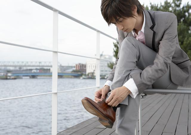 靴ひもを結ぶ若い男性の写真素材 [FYI03047655]