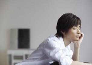 頬杖をつく若い男性の写真素材 [FYI03047686]