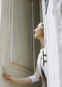 ドアを開ける若い女性の写真素材 [FYI03047932]