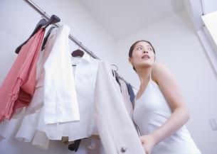 クローゼットから服を選ぶ女性の写真素材 [FYI03048140]
