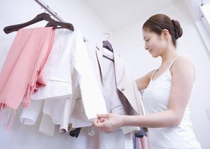 クローゼットから服を選ぶ女性の写真素材 [FYI03048141]