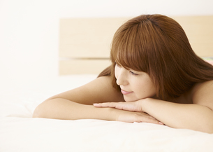 ベッドに横たわるミドル女性の写真素材 [FYI03048245]
