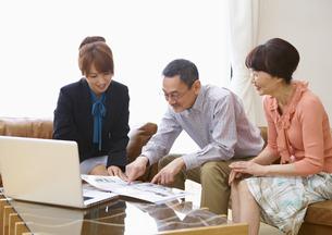 保険外交員の女性とシニア夫婦の写真素材 [FYI03048251]