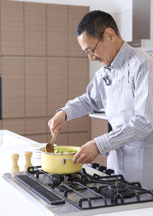 料理をするシニア男性の写真素材 [FYI03048275]