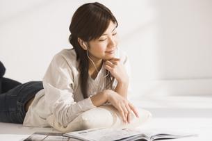 音楽を聞きながら雑誌を読む女性の写真素材 [FYI03048335]