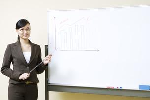 ホワイトボードの横に立つ女性の写真素材 [FYI03048391]