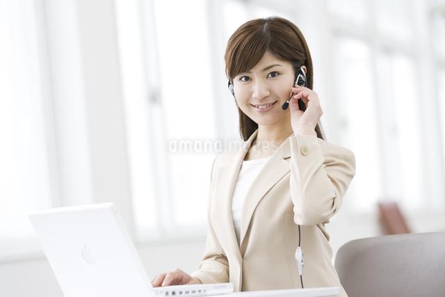 インカムをつけた笑顔の女性の写真素材 [FYI03048477]