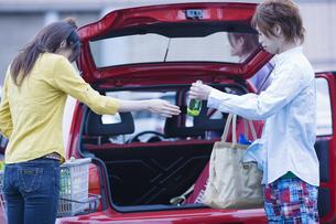 車に荷物を積むカップルの写真素材 [FYI03048831]