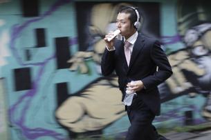 物を食べながら走るビジネスマンの写真素材 [FYI03049189]