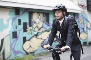 ヘルメットをして自転車に乗るビジネスマンの写真素材 [FYI03049204]
