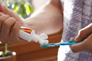 歯ブラシに歯磨き粉を出す手の写真素材 [FYI03049254]