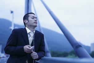 音楽を聴くビジネスマンの写真素材 [FYI03049258]