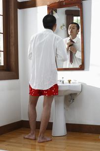 鏡を見ながらネクタイをしめる男性の写真素材 [FYI03049292]