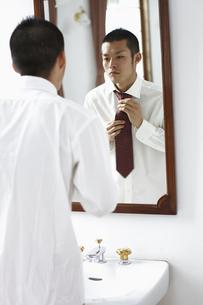 鏡を見ながらネクタイをしめる男性の写真素材 [FYI03049293]