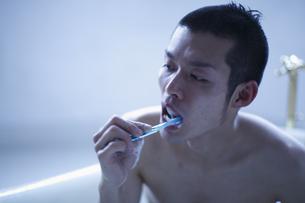 歯磨きをしながら入浴する男性の写真素材 [FYI03049311]