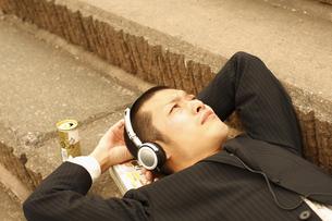 階段で寝そべって音楽を聴くビジネスマンの写真素材 [FYI03049329]