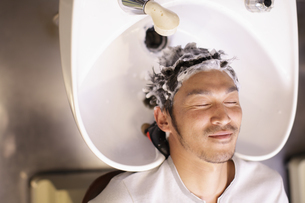 シャンプー台で髪を洗われる男性の写真素材 [FYI03049343]