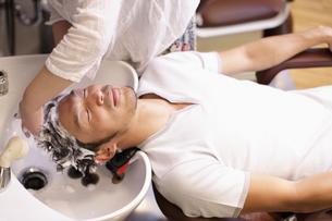 シャンプー台で髪を洗われる男性の写真素材 [FYI03049345]