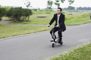 電動スクーターに乗るビジネスマンの写真素材 [FYI03049346]
