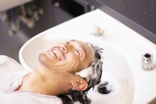 シャンプー台で髪を洗われる男性の写真素材 [FYI03049349]
