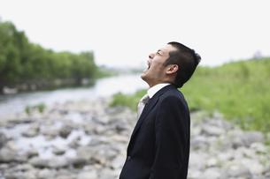 川辺で叫ぶビジネスマンの写真素材 [FYI03049356]