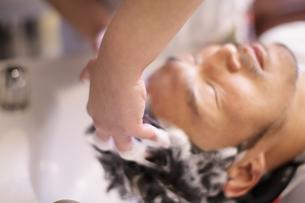 シャンプー台で髪を洗われる男性の写真素材 [FYI03049362]