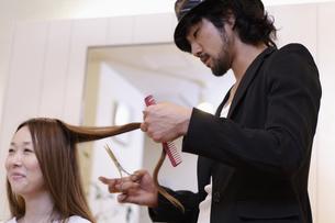 女性の髪をカットする美容師の写真素材 [FYI03049416]
