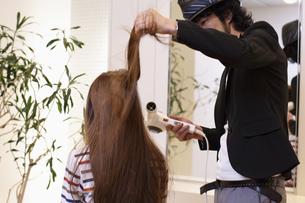 女性の髪を乾かす美容師の写真素材 [FYI03049420]
