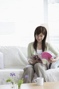 ソファーで雑誌を読む女性の写真素材 [FYI03049533]