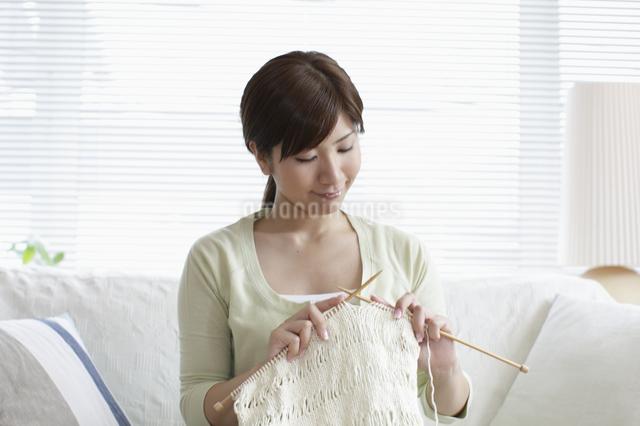 ソファーで編み物をする女性の写真素材 [FYI03049542]
